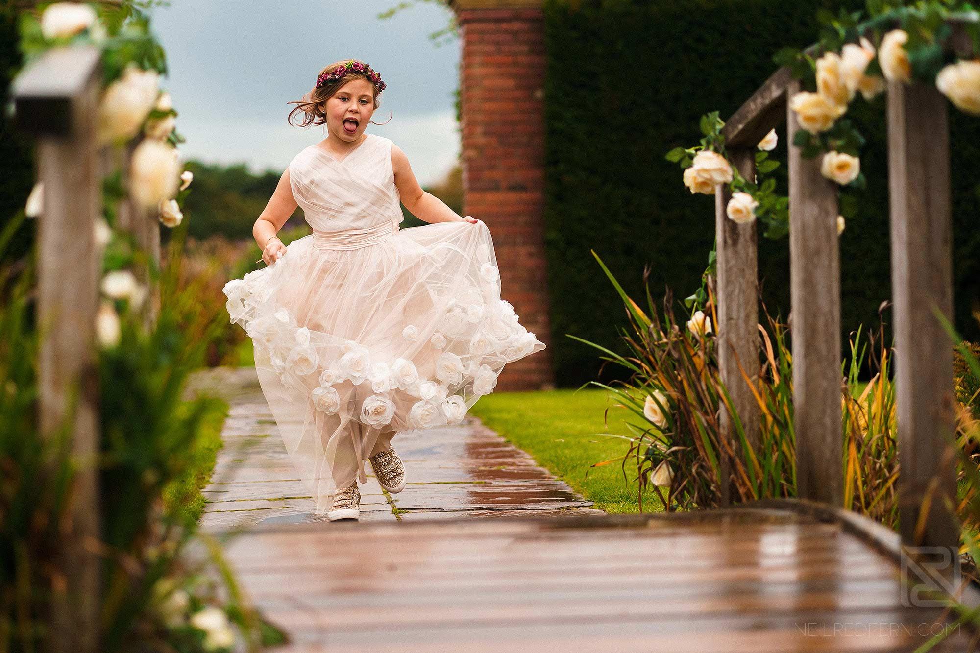 bridesmaid running through Abbeywood Estate gardens