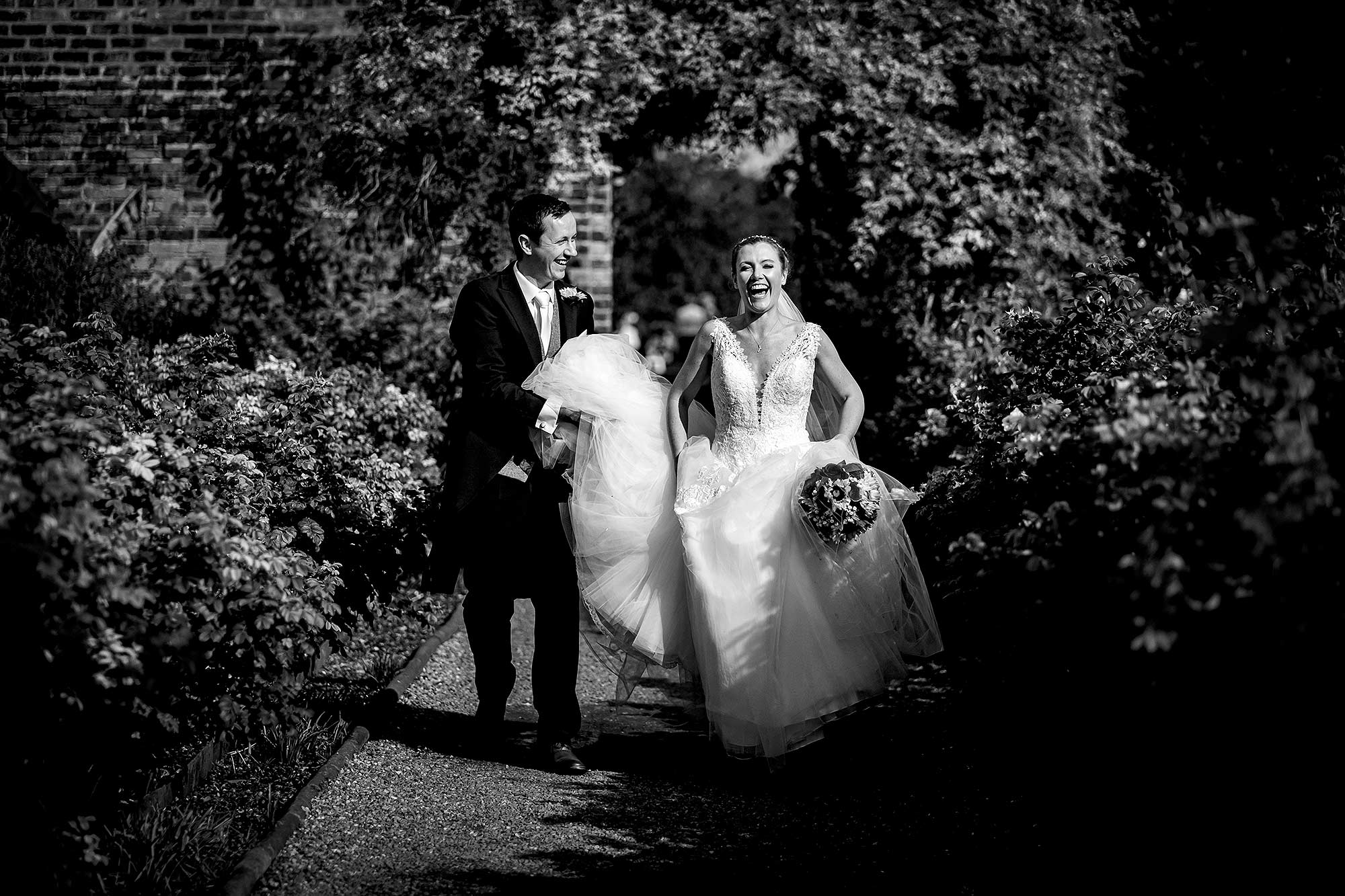creative portrait of bride and groom laughing together at Arley Hall