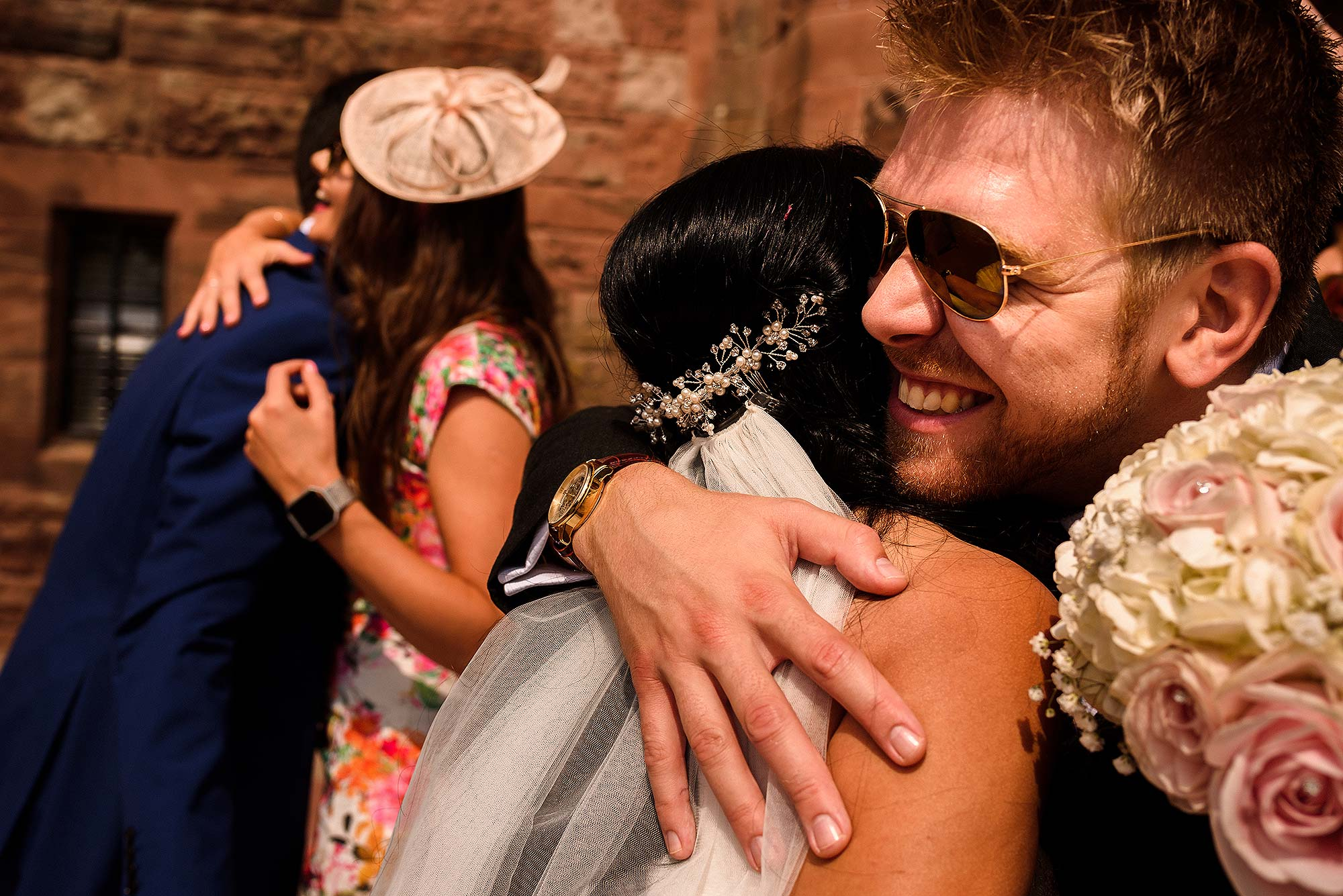 documentary photograph of friends hugging bride and groom