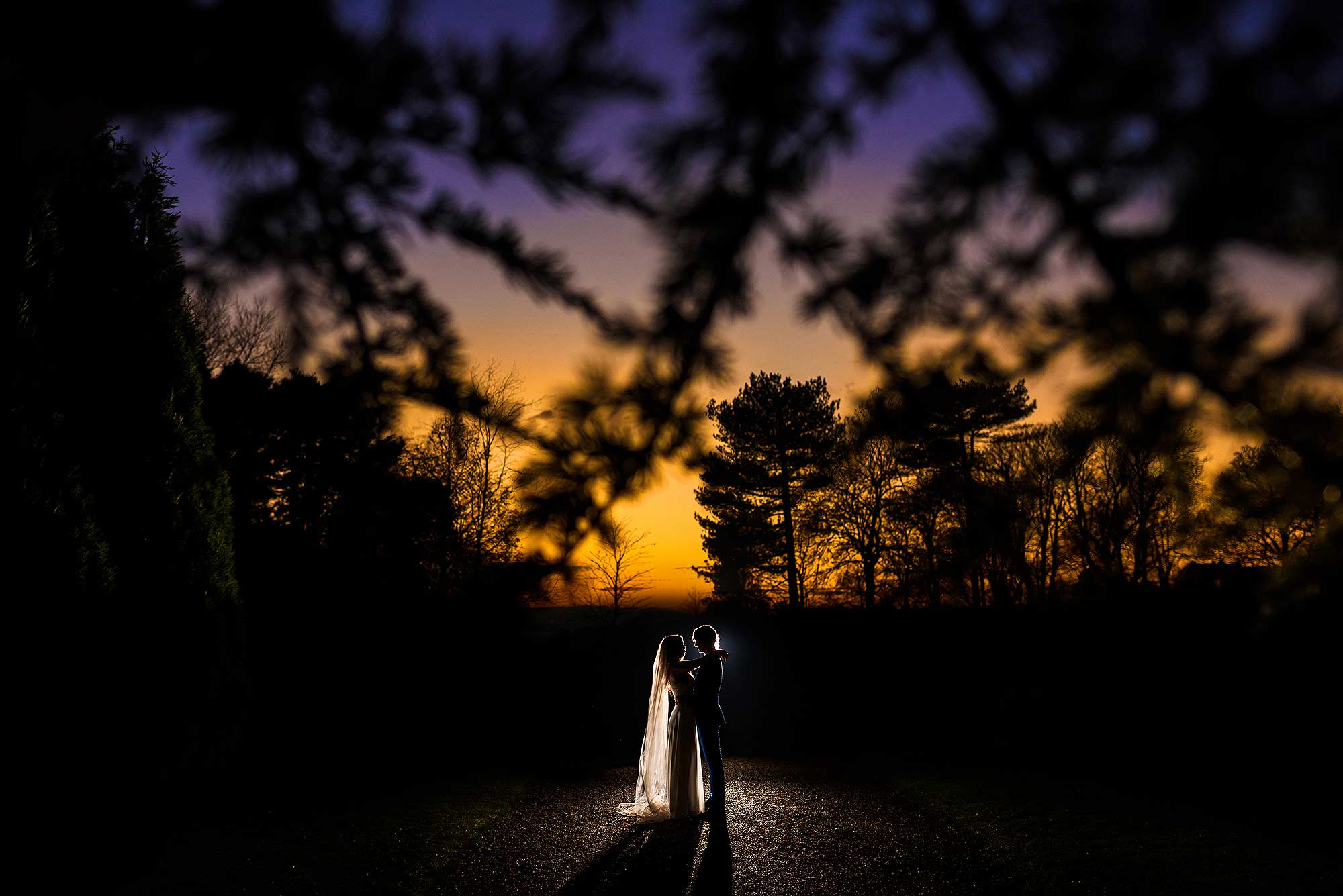 unique portrait of bride and groom stood outside at nighttime with colourful sky