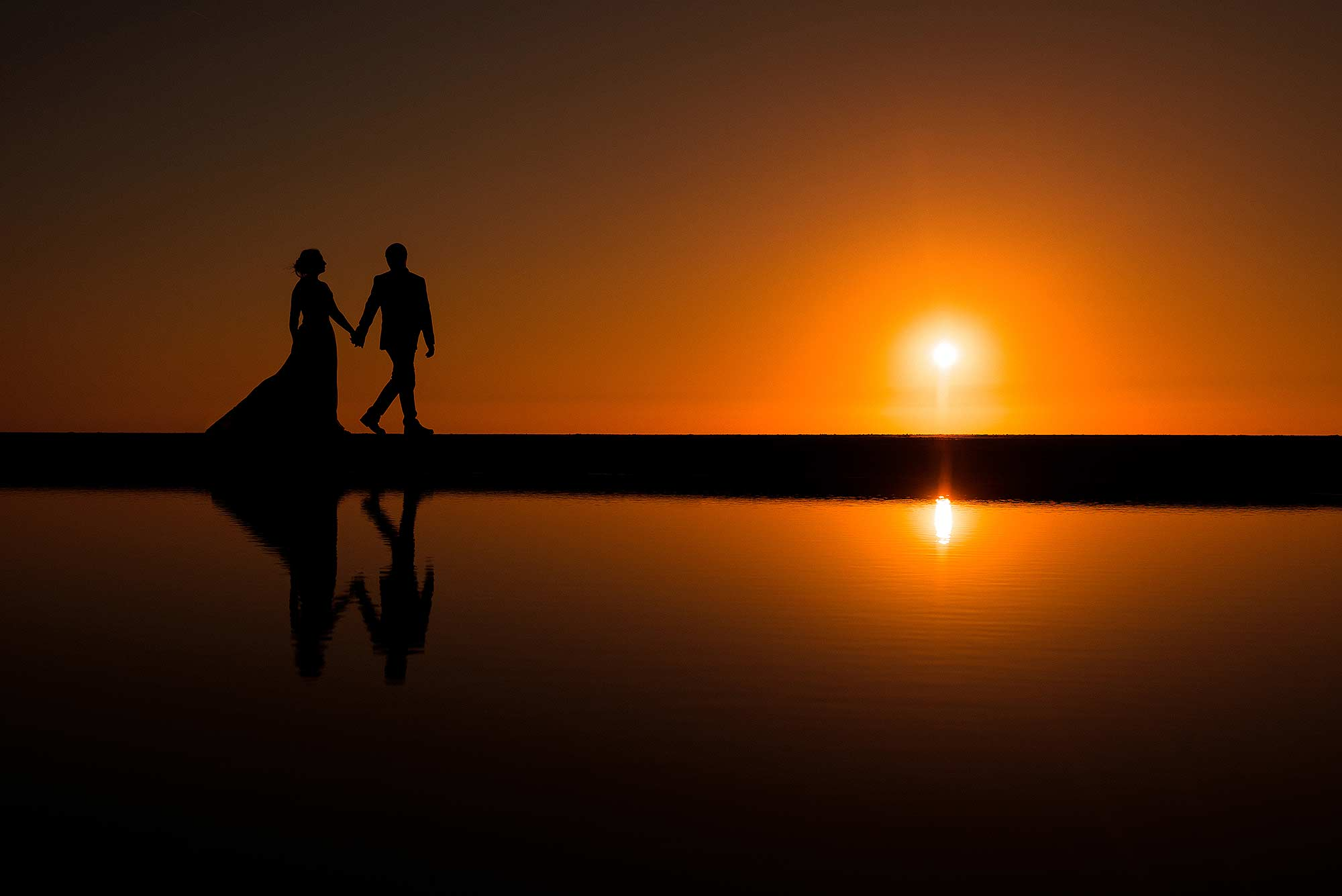 beautiful silhouette photograph of bride and groom at sunset