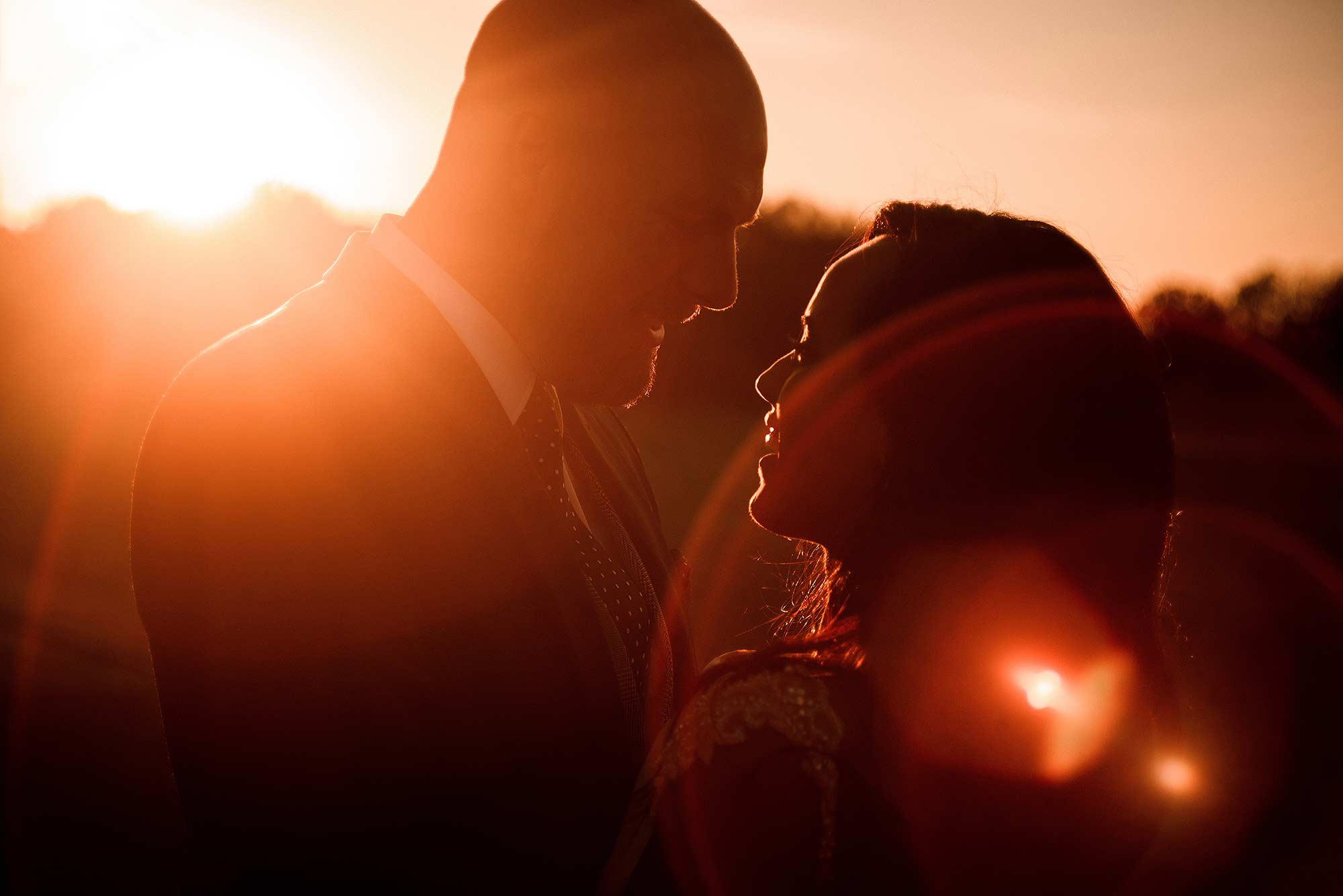 relaxed sunset portrait of bride and groom at sunset with flare