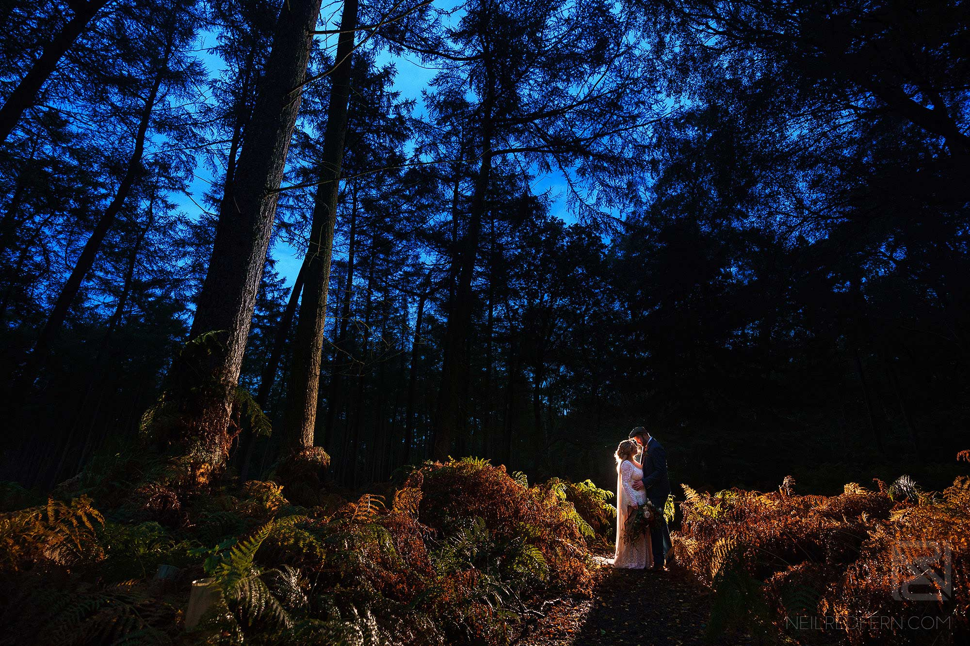 creative night time portrait of bride and groom in forest
