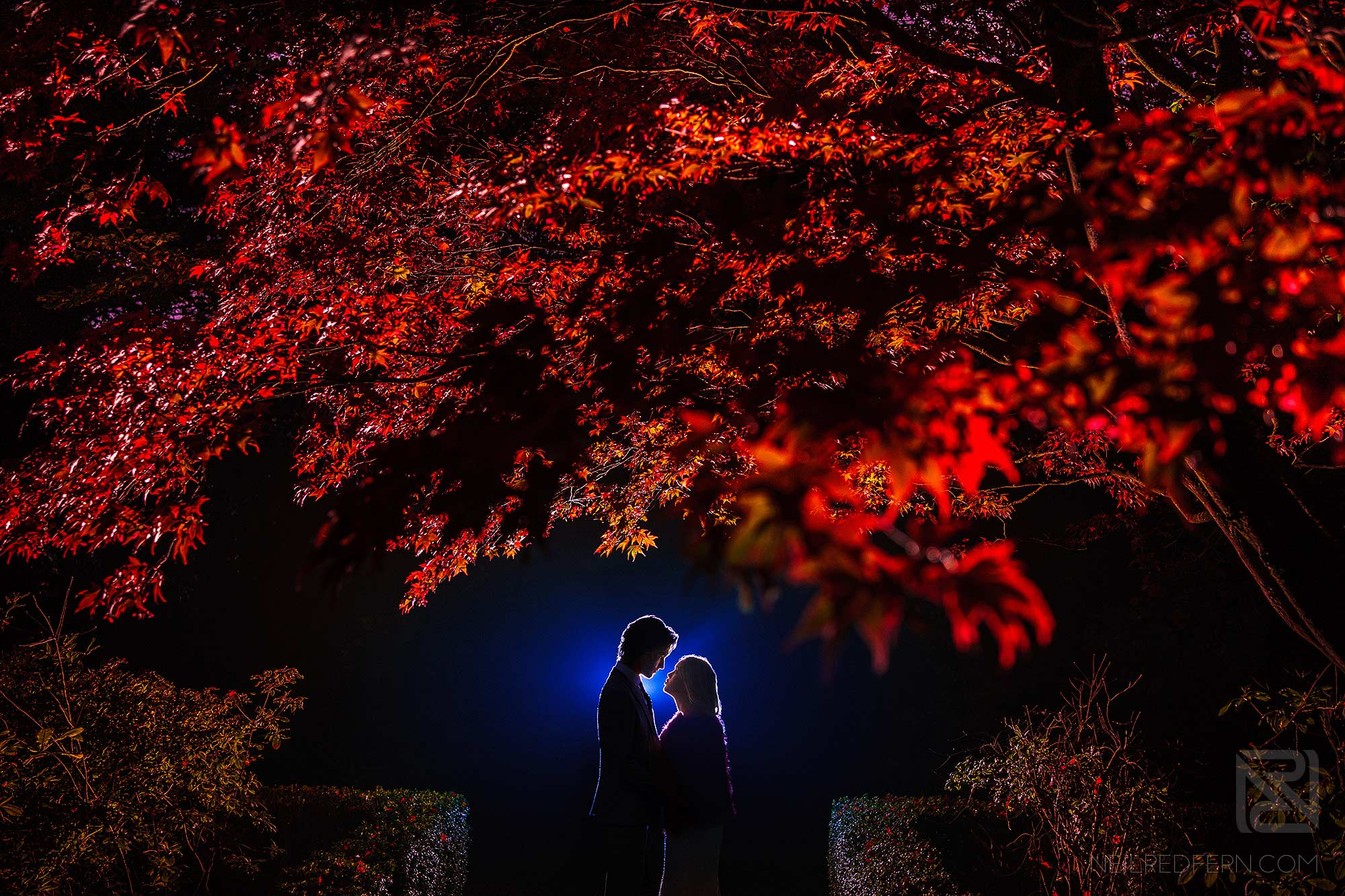 creative photograph of night time portrait of bride and groom outside Eaves Hall