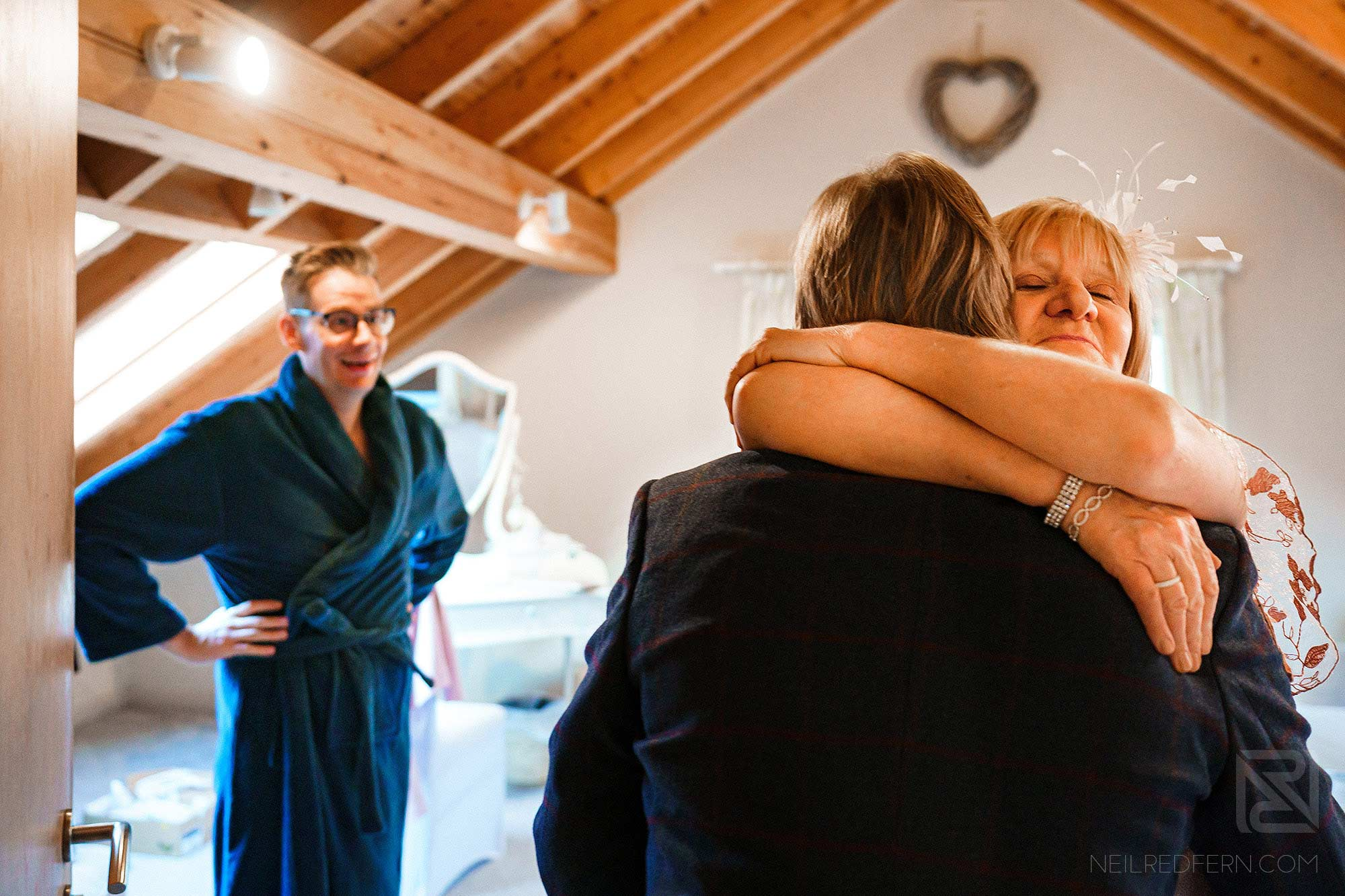 groom's parents hugging on wedding morning