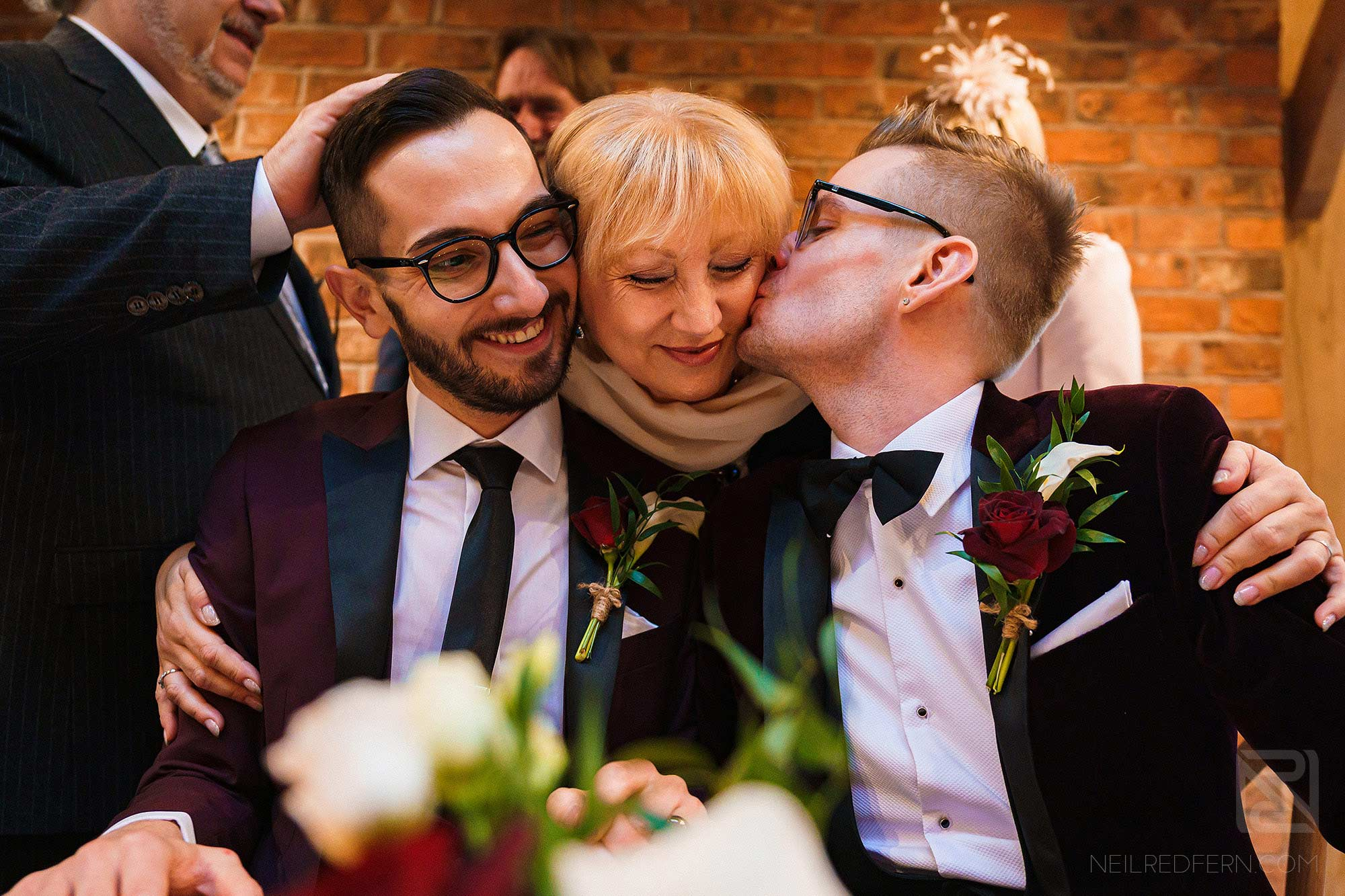 happy grooms kissing guest during signing of register