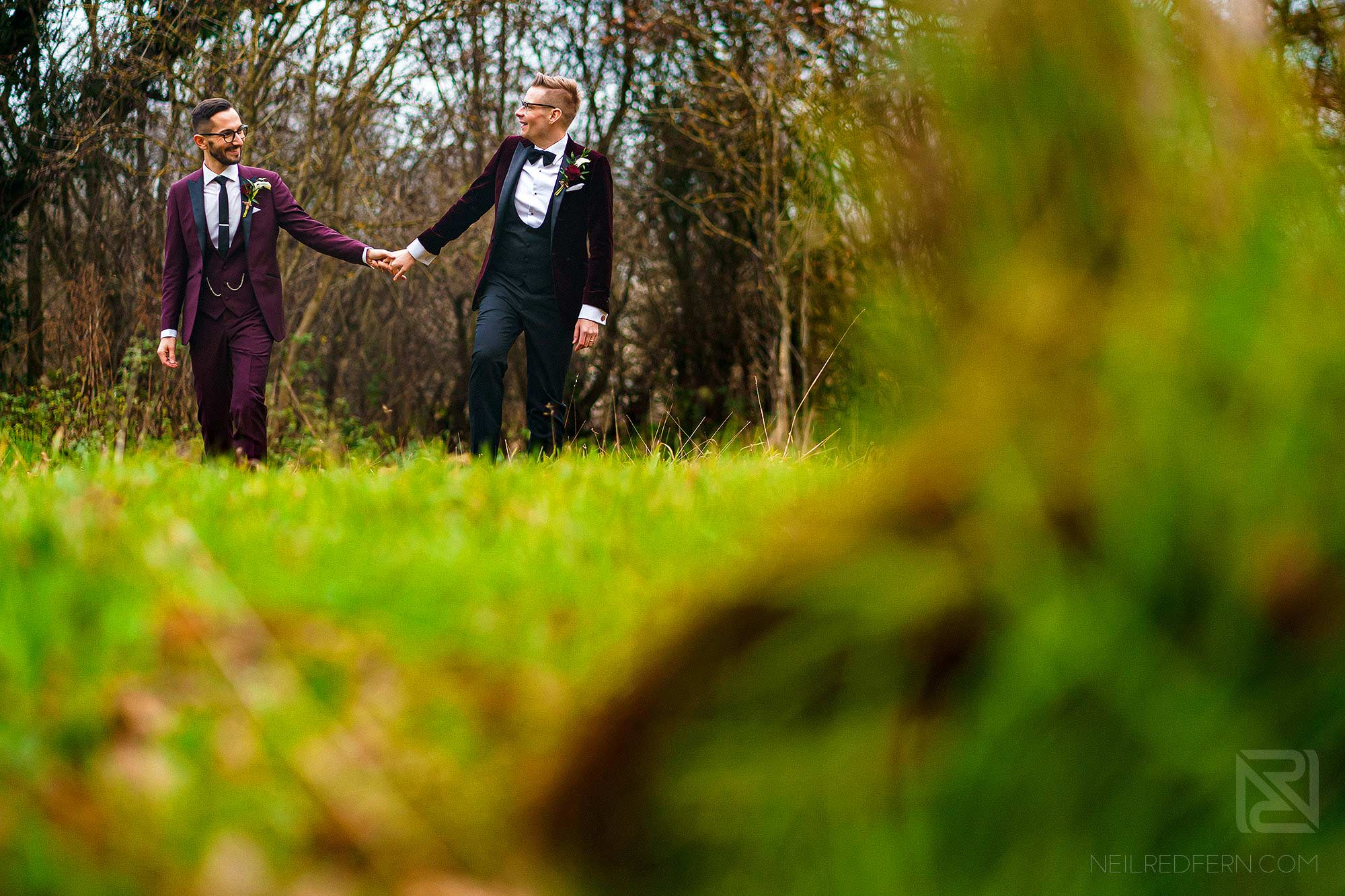 happy grooms walking through the grass at the Oak Tree of Peover winter wedding