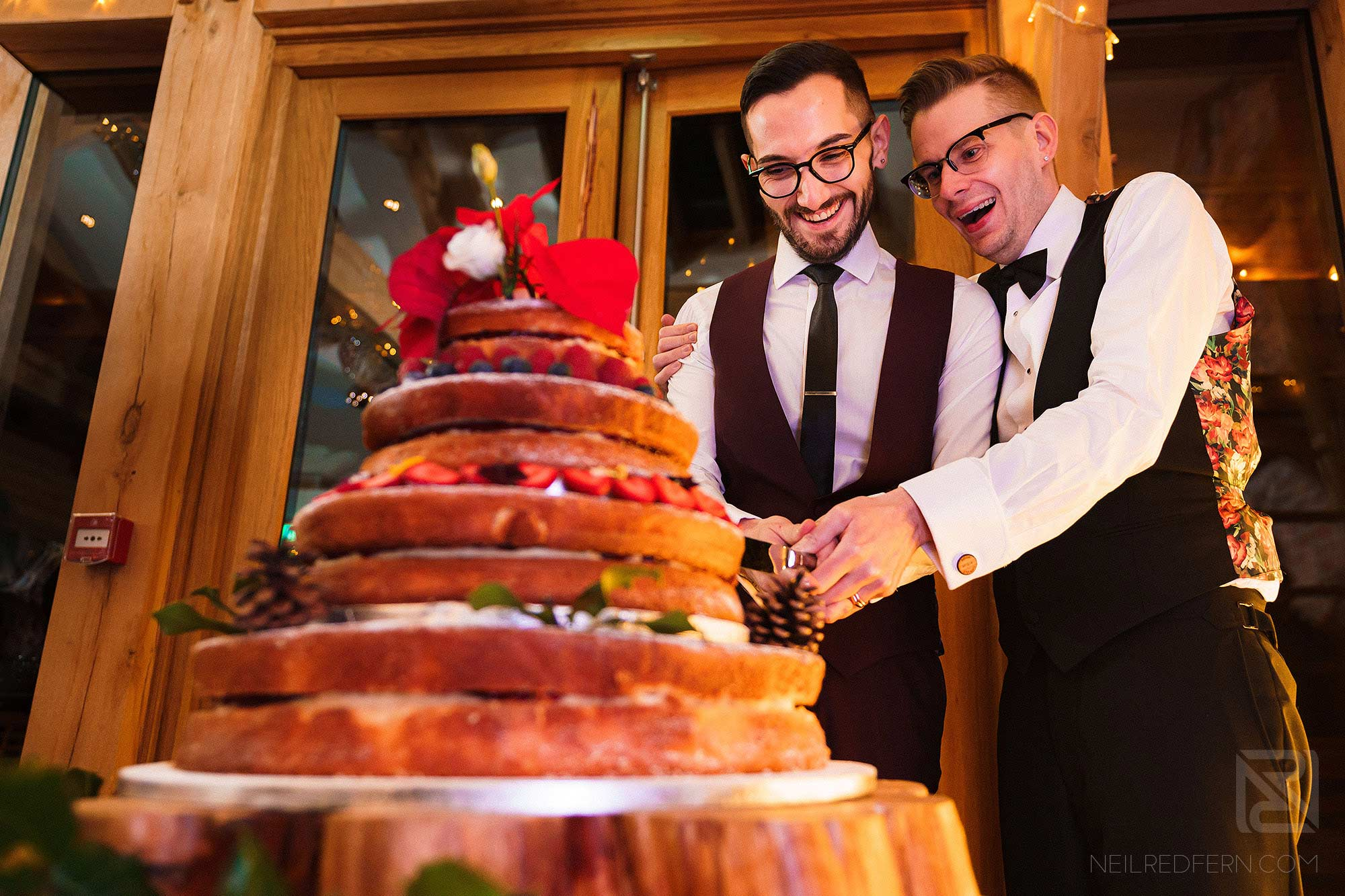 two grooms cutting wedding cake