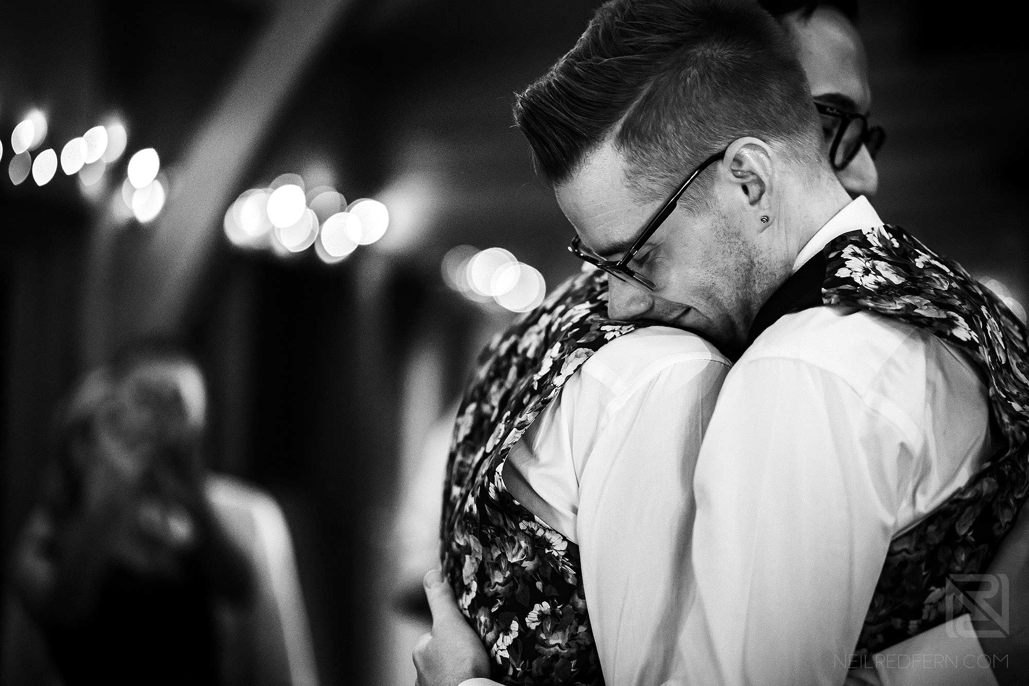 grooms hugging each other during first dance