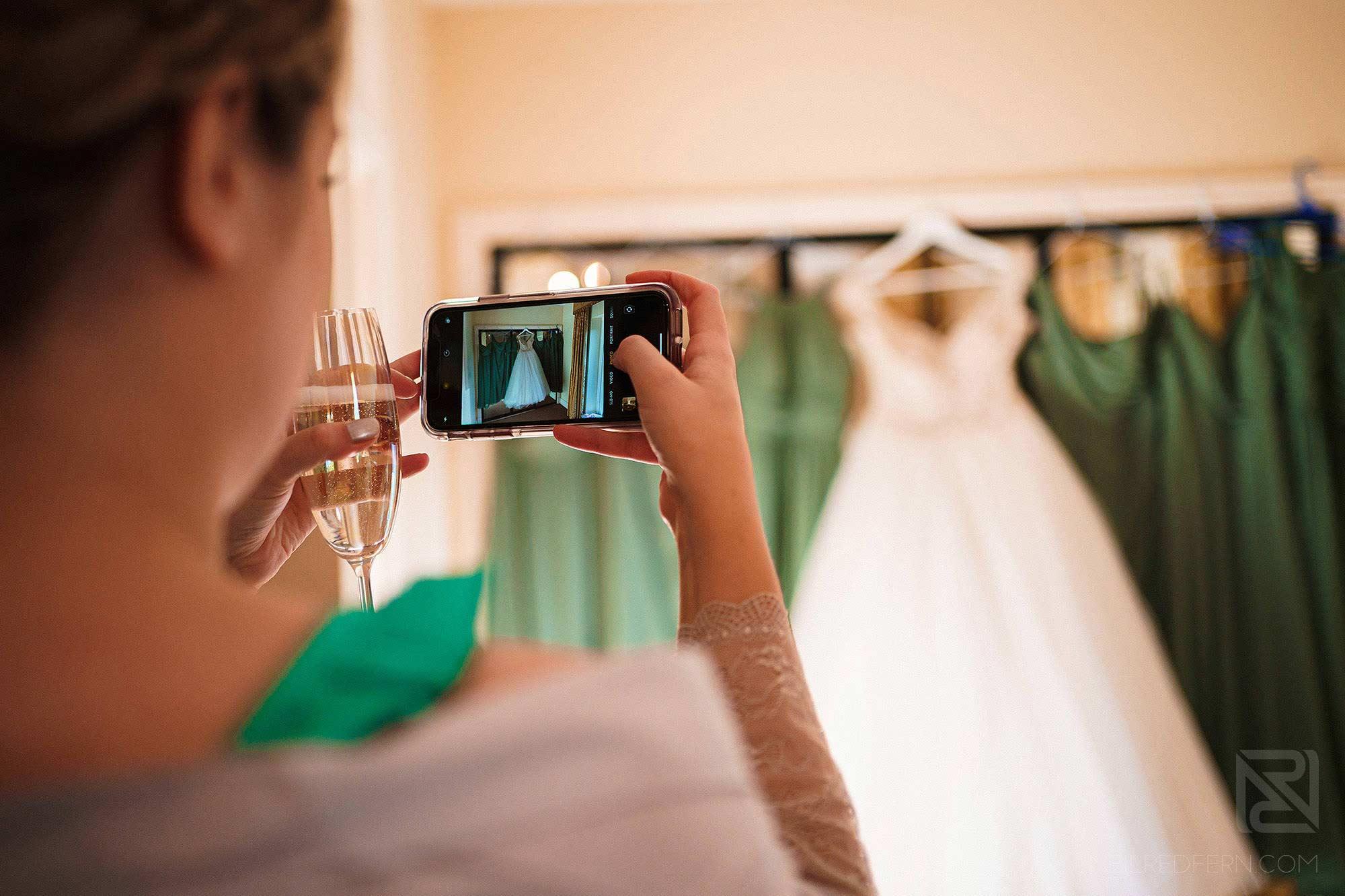 bridesmaid taking photograph of wedding dress