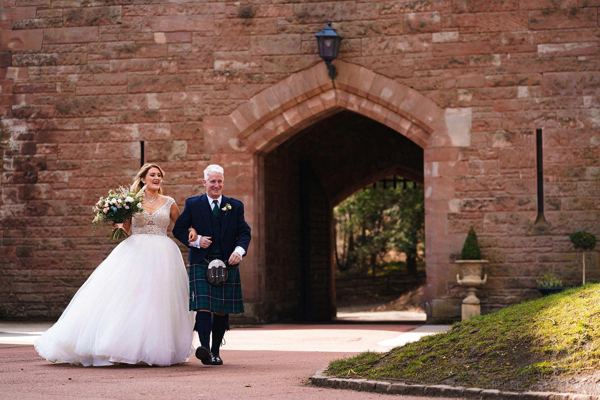 bride and father walking towards Peckforton Castle