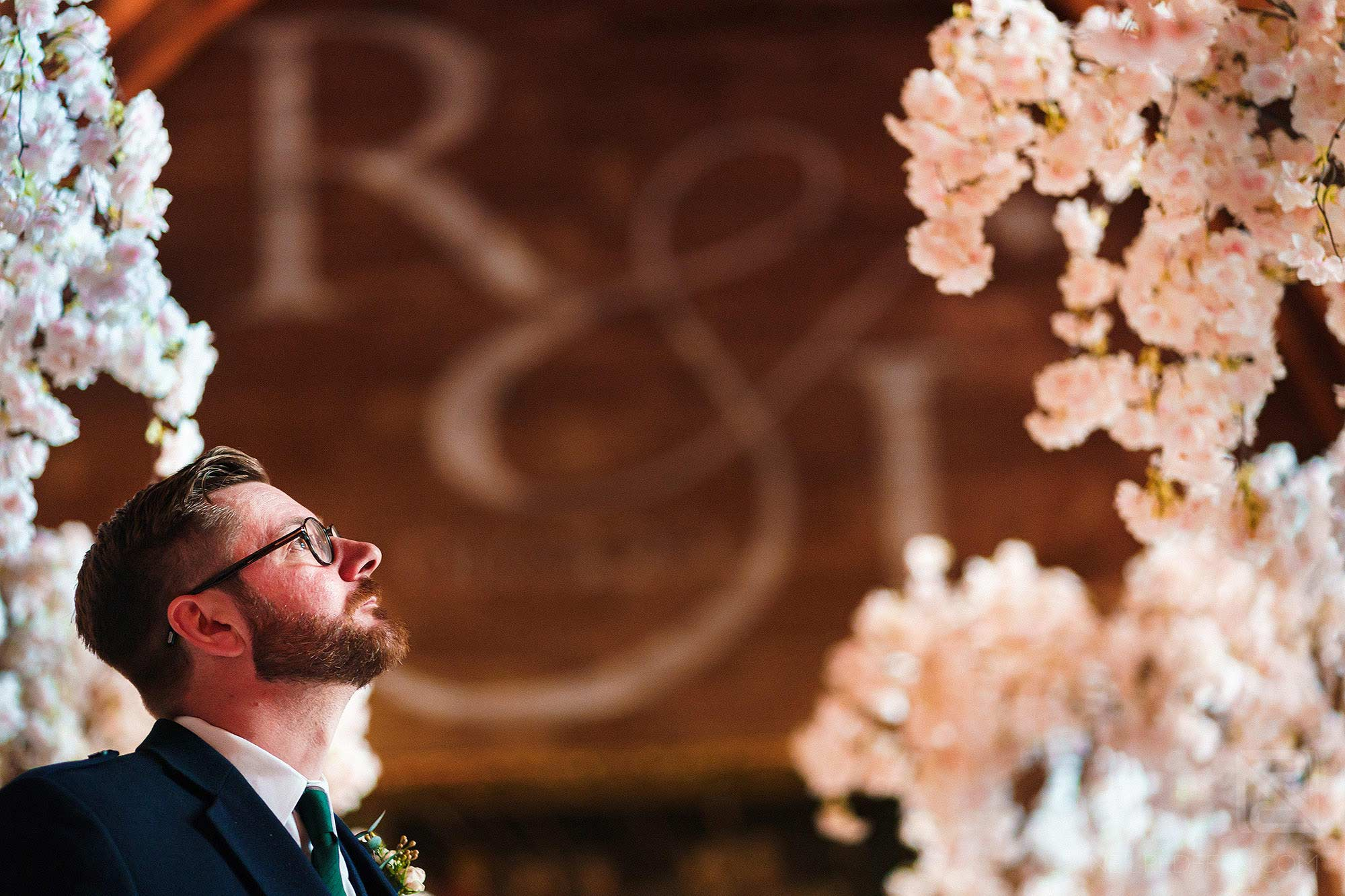 groom waiting nervously at top of the aisle