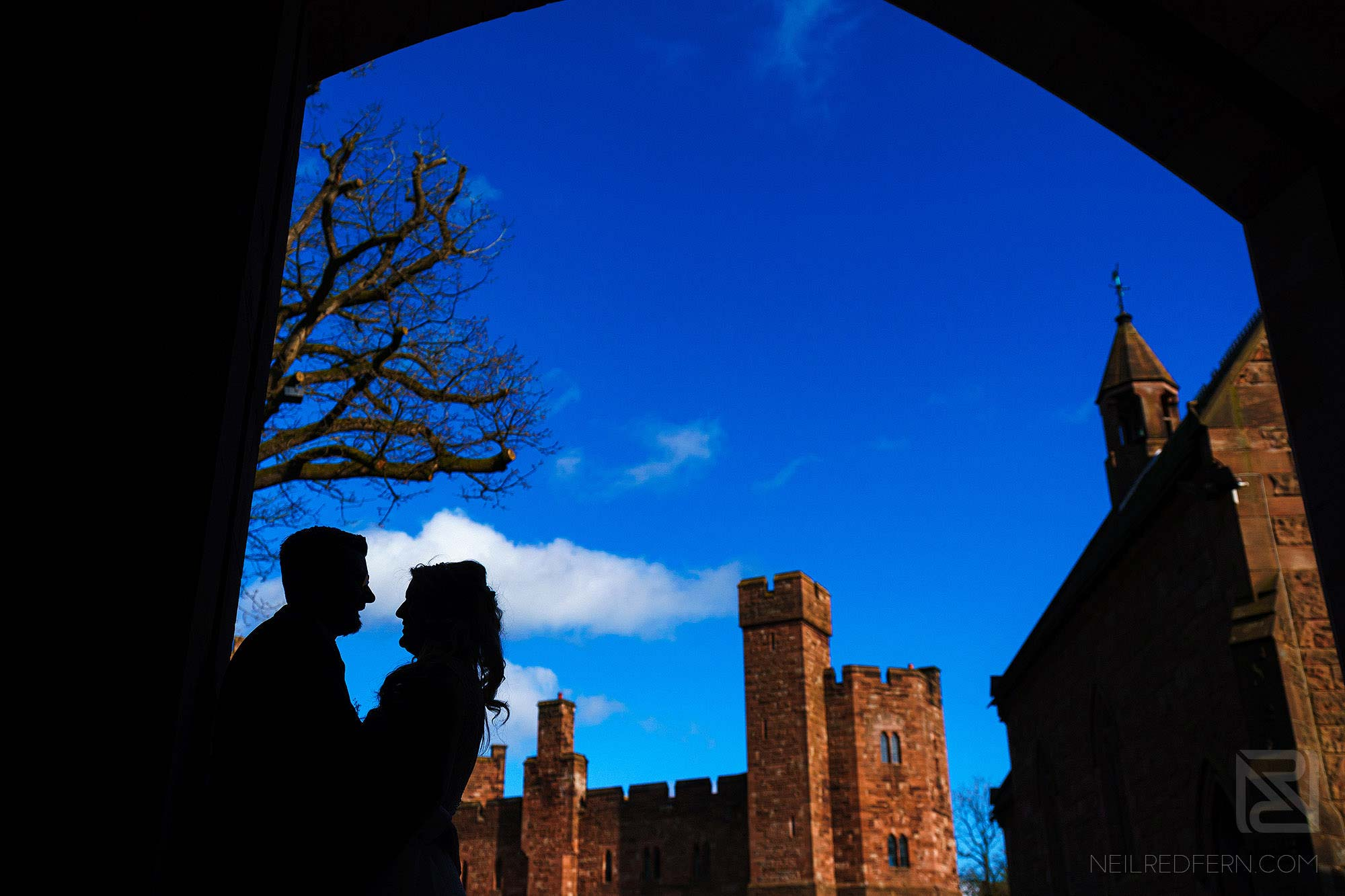silhouette photograph of bride and groom outside Peckforton Castle