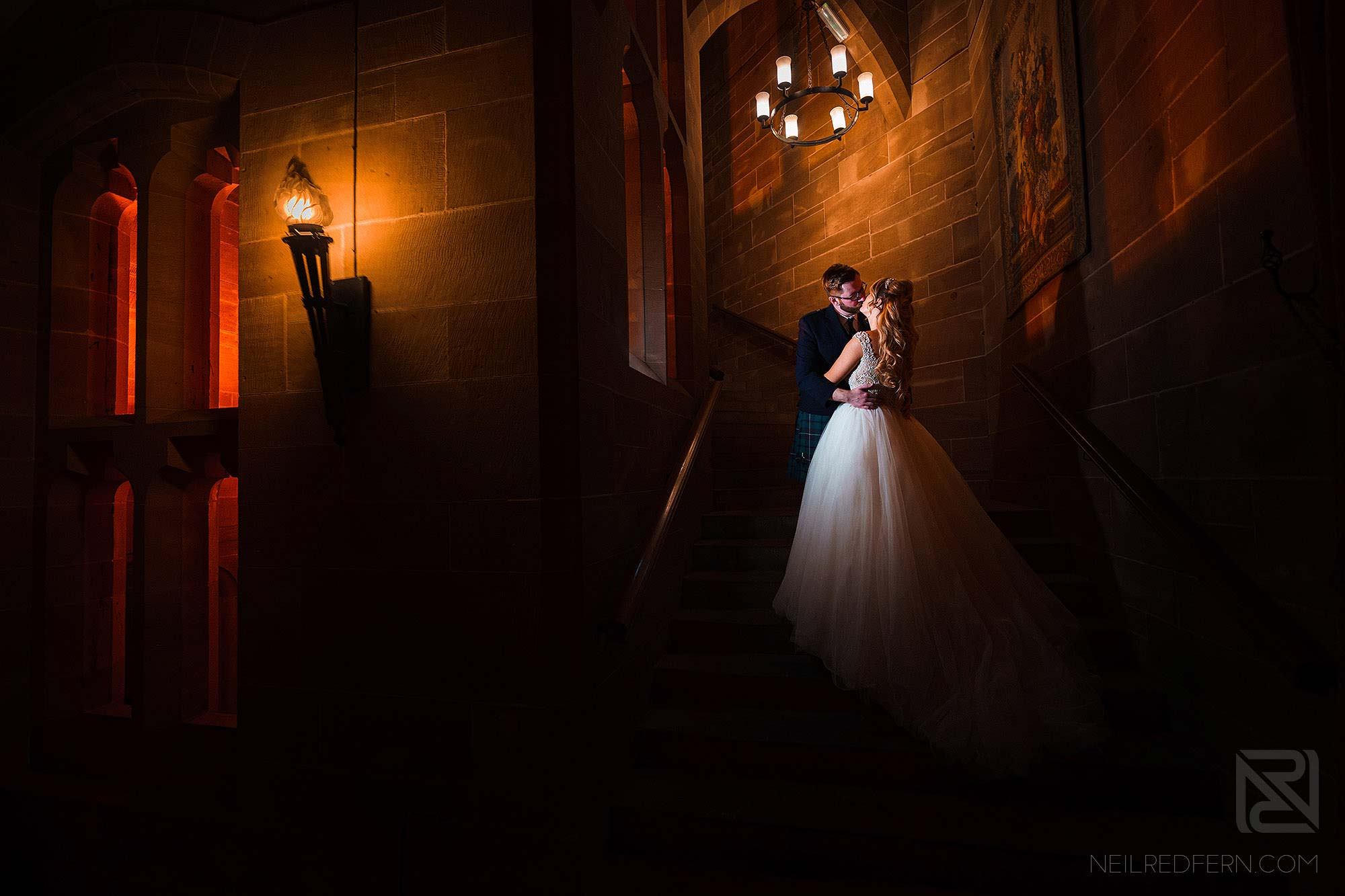 photograph of bride and groom on stairs in Peckforton Castle