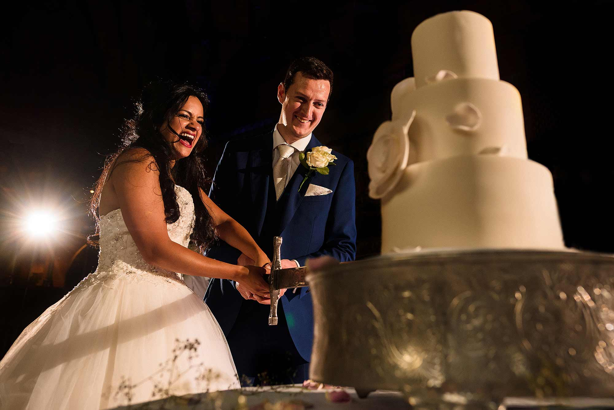 bride and groom cutting wedding cake at Peckforton Castle